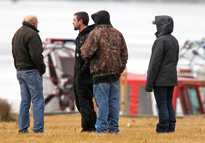 H. Rick Bamman -hbamman@shawmedia.com Friends and family members watch as ice divers begin the search in Pistakee Bay Saturday morning for the body of a missing angler that fell through the ice Friday evening.