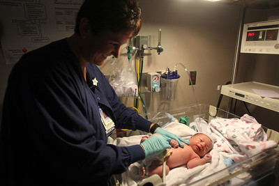 Lance Booth - lbooth@shawmedia.com Patricia Monaghan, of Woodstock, checks the vitals of Josiah Kloss labor and delivery department at Centegra Medical Center in Woodstock on Monday, February 6, 2012. Monaghan works the night shift at the hospital as a nurse and has to leave her three children with her husband.