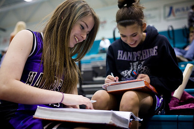 Jenny Kane - jkane@shawmedia.com Hampshire sophomore Krista Balisteri, (left) does homework with freshman Kylie Incapreo, (right) on the bleachers during the varsity game against Woodstock North.