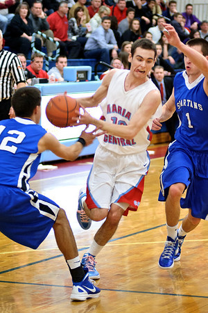 Daniel J. Murphy - dmurphy@shawmedia.com  Marian Central guard Will Kaufmann splits St. Francis defenders Tim Zettinger (left) and Brian Spahn (right) on a drive to the basket Friday February 10, 2012 at Marian Central High School in Woodstock. St. Francis defeated Marian Central 61-42.