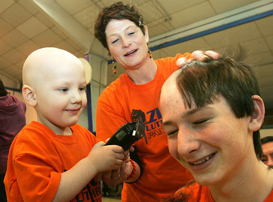 H. Rick Bamman - hbamman@shawmedia.com Sean Keller (left) with help from mom Valerie Keller clips the hair of his older brother Max Keller during a shave-a-thon at Zion Lutheran School in Marengo. The four year-old is fighting Luekemia.