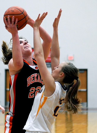 Sarah Nader - snader@shawmedia.com DeKalb's Emily Bemis (left) shoots over Hononegah's Karley Kolberg  during the second quarter of Monday's Class 4A McHenry Sectional in McHenry on February 20, 2012