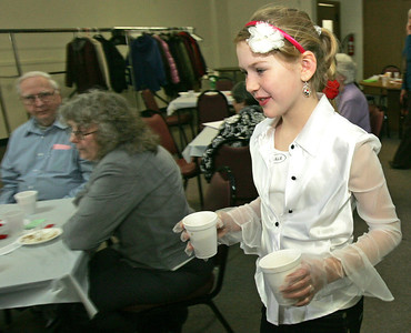 H. Rick Bamman - hbamman@shawmedia.com  Girl Scout Lillie Korpalski serves coffee to seniors at the Senior Center in Crystal Lake Monday February, 20. Troop 421 of Crystal Lake hosted the lunch party for the seniors serving hot dogs, baked beans, potato chips and dessert. The scouts also performed musical numbers during the event.