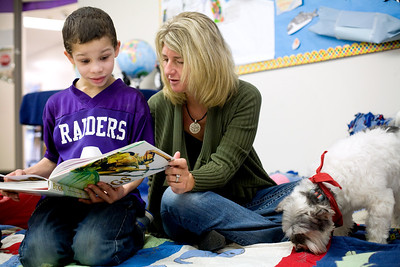 Jenny Kane - jkane@shawmedia.com Becky Monroe and her rescue dog Thorp listen as third grader Verrick Jones, 9, reads to them about insects at the Clay Academy. It was Monroe's first time back reading to the children after traveling to Antarctica.