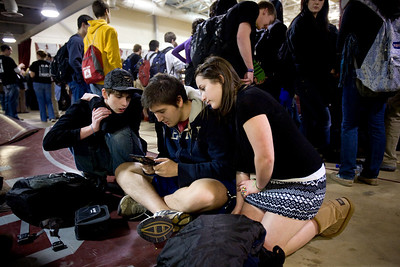 Jenny Kane - jkane@shawmedia.com Wed. Feb. 22, 2012, Prairie Ridge students Haven Comeaus, junior, (right), Evan Czonstka, senior, (center) and Kevin Porter, senior, (left) look at a game Czonstka is playing during an all school assembly held at the high school in Crystal Lake.