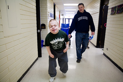 Jenny Kane - jkane@shawmedia.com Wed. Feb. 22, 2012, Coast Guard veteran Jason Paddock, of McHenry, walks with Francis Weir after an assembly at the Special Education District of McHenry County Education Center in Woodstock for Take a Veteran to School Day.