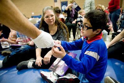 Jenny Kane - jkane@shawmedia.com Wed. Feb. 22, 2012, Peggy Wold watches as Ricky Trinidad receives a box of candy from a veteran during an assembly at the Special Education District of McHenry County Education Center in Woodstock for Take a Veteran to School Day.