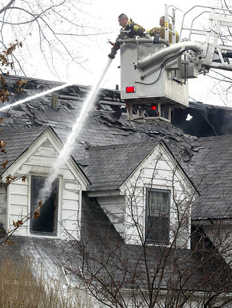 H. Rick Bamman -hbamman@shawmedia.com Firefighters pour water into a home at 906 Garfield in Harvard Thursday morning. Fire units from Hebron, Walworth, Fontana and Sharon, Wisc., Capron Richmond, Linn Township, Boone County, Lakewood, Marengo and Woodstock are providing mutual assistance.