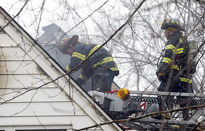 H. Rick Bamman -hbamman@shawmedia.com Firefighters cut a hole into the roof to vent the attic of the home at 906 Garfield in Harvard.