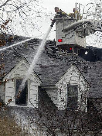 H. Rick Bamman -hbamman@shawmedia.com Firefighters pour water into the home.