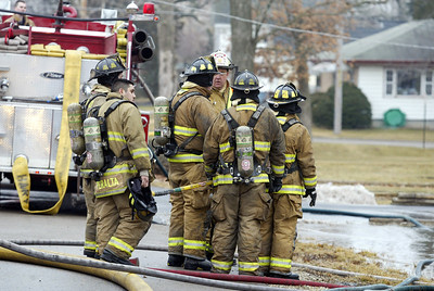 H. Rick Bamman -hbamman@shawmedia.com A group of firefighters are briefed before entering the home.