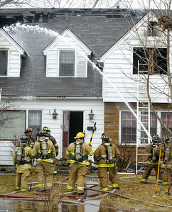 H. Rick Bamman -hbamman@shawmedia.com Firefighters stage at the front of the home.
