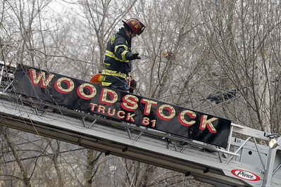 H. Rick Bamman -hbamman@shawmedia.com A firefighter makes his way back down after cutting a vent in the roof of the home.