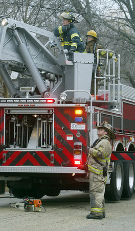 H. Rick Bamman -hbamman@shawmedia.com Firefighters watch colleagues work on the roof of the home at 906 Garfield in Harvard.