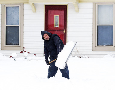 H. Rick Bamman -hbamman@shawmedia.com Algonquin resident Angel Lopez clears the walk in front of his Perry Drive home on Friday morning. Saturday is expected to be partly sunny with a highs in the low 30's.
