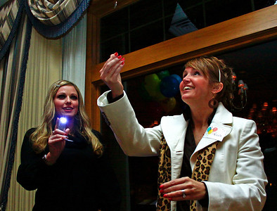 Brett Moist - For Shaw Media Deanna Kell (left) watches Nicole Prihoda flip the coin for the heads/tails game during the annual awards dinner at the Boulder Ridge Country Club in Lake in the Hills on Friday, February 17th. This award ceremony marked 60 years in the community.
