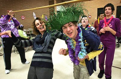 "H. Rick Bamman -hbamman@shawmedia.com SEDOM Teacher Karen Raguet leads the Limbo line with Zakary Thompson as they see how low they can go to kick off the 2012  ""Heat Wave "" Homecoming Beach party at the Woodstock school. Students and staff participated an beach themed activities including a Tikie Hut photo booth, pin the apple on the roast pig, beach ball toss and dancing to the music of the Beach Boys. The  homecoming game and dance will be held at Northwood Elementary school on Friday."