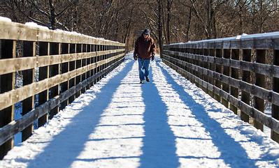 """Kyle Grillot - kgrillot@shawmedia.com   Paul Sawczuk of Algonquin takes advantage of the sunny weather to take a walk along the Prairie Trial crossing the Fox River Monday, February 3, 2014. """"This is the first time I've been on a walk in a while,"""" said Sawczuk. Though he expects a change in weather through the week."""
