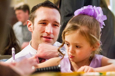 """Kyle Grillot - kgrillot@shawmedia.com   Damon Hill of Woodstock Watches his daughter Morgan, 5, make crafts during a break from dancing at the Cinderella Daddy Daughter Ball Friday in Crystal Lake. """"I remember my dad doing this years ago with my sister,"""" said HIll, """" and now I get to myself."""" The event, sponsored by the Crystal Lake Park District, sold out all 150 tickets for the event."""