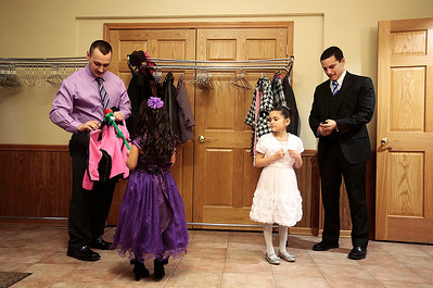 Kyle Grillot - kgrillot@shawmedia.com   Mike Woods of Huntley (left) and Michael Langlois of Crystal Lake helps their daughters Mia,6, and Kimberly,5, with their jackets at the Cinderella Daddy Daughter Ball Friday in Crystal Lake. The event, sponsored by the Crystal Lake Park District, sold out all 150 tickets for the event.