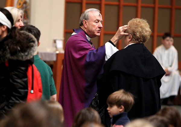 Sandy Bressner - sbressner@shawmedia.com<br /> Monsignor Joseph Linster places ashes on a parishioner's forehead during a mass for Ash Wednesday at St. Patrick's Church in St. Charles.