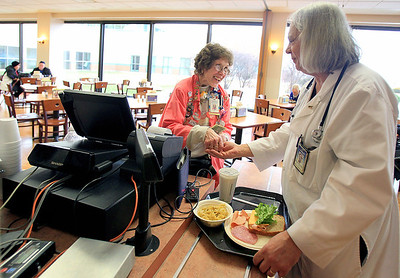Sarah Nader - snader@shawmedia.com Sue Manderscheid (left) of McHenry rings us Warren Mavrinac of Crystal Lake while volunteering in the cafeteria at Centegra Hospital in McHenry. Despite having a brain injury, Manderscheid  had volunteered more than 4,000 hours at the hospital cafeteria.
