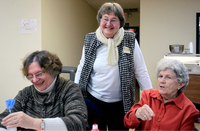 Sarah Nader - snader@shawmedia.com Carol Lee (center) of Johnsburg greets Carol Curran (left) of McHenry and Rosalyn Kollenkark of McHenry while working at Senior Services in Johnsburg.