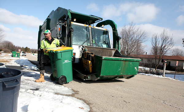 "Sandy Bressner - sbressner@shawmedia.com<br /> McCree ""Mac"" Davis of Maple Park unloads recycled materials into his Waste Management truck during his route through Campton Hills Monday morning."