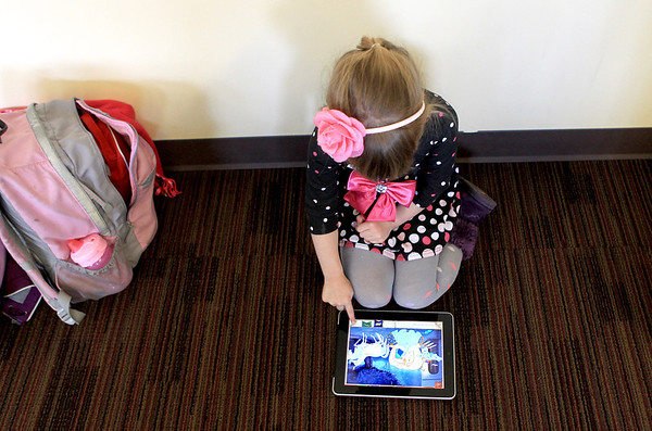 Sandy Bressner - sbressner@shawmedia.com<br /> Emma Korbel, 4, of Elgin plays a game on an iPad during a meeting of the Positive Connection homeschool support group at the Brewster Creek Lodge in St. Charles Township Friday afternoon.
