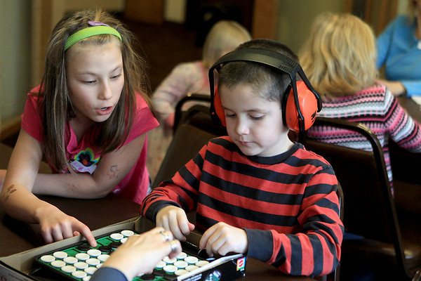 Sandy Bressner - sbressner@shawmedia.com<br /> Aria King, 9, of Bartlett helps Collin Blackman, 6, of West Dundee with his next move in a game of Othello during a meeting of the Positive Connection homeschool support group at the Brewster Creek Lodge in St. Charles Township Friday afternoon.