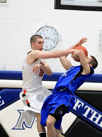 Sandy Bressner - sbressner@shawmedia.com<br /> St. Charles East's Luke Ludke (left) blocks a shot by Quinten Payne of St. Charles North during East's 63-50 regional game win over St. Charles North Wednesday.