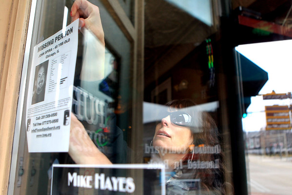 Sandy Bressner - sbressner@shawmedia.com<br /> Stephanie Spira McNeil hangs a sign in the window of Pub 222 in St. Charles Wednesday afternoon to help bring attention to the five year anniversary of the disappearance of her brother, John Spira. John Spira of St. Charles disappeared Feb. 23, 2007 and was last seen at his business, Universal Cable Construction in West Chicago.