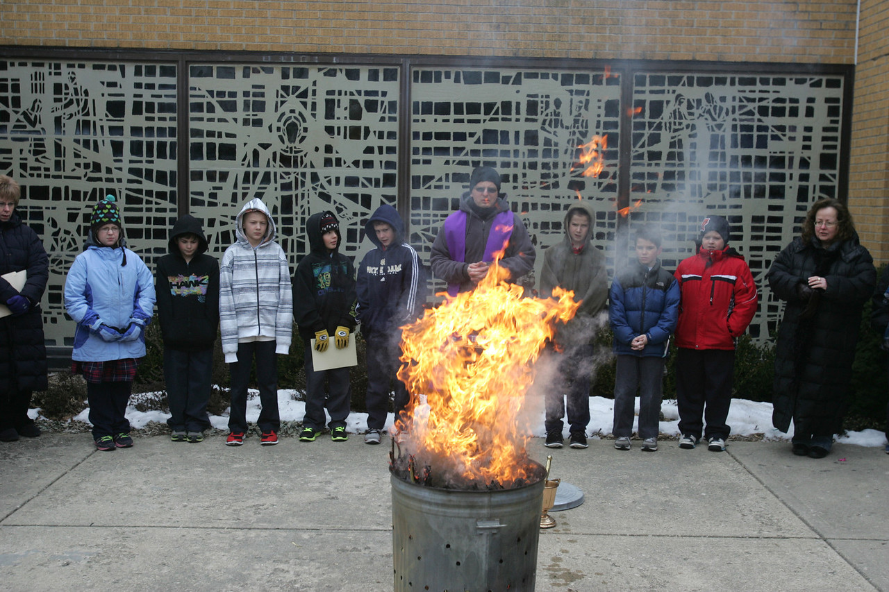 """H. Rick Bamman - hbamman@shawmedia.com Fr. Andrzej Brezinski conducts the palm burning celebration  Tuesday, Feb. 12, 2013 at St. Margaret Mary Church as St Margaret Mary School students from Sally Quinlan and Nicole Hinds'  fifth grade classes sing """" Jesus Remember Me."""" Traditionally, the ashes for the Ash Wednesday service come from burning the palm fronds from the previous year's Palm Sunday celebration."""