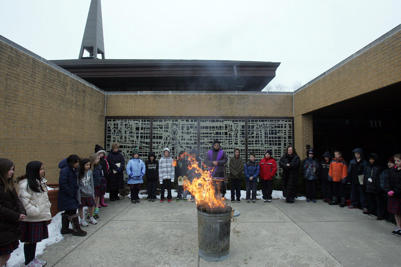 "H. Rick Bamman - hbamman@shawmedia.com Fr. Andrzej Brezinski conducts the palm burning celebration  Tuesday, Feb. 12, 2013 at St. Margaret Mary Church as St Margaret Mary School students from Sally Quinlan and Nicole Hinds'  fifth grade classes sing "" Jesus Remember Me."" Traditionally, the ashes for the Ash Wednesday service come from burning the palm fronds from the previous year's Palm Sunday celebration."