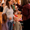 Amy Scialo receives her ashes as her son, Dominic, 3, and daughter Mia, 6, look on from Julie Testa during an Ash Wednesday Mass at St. John Neumann Church in St. Charles.