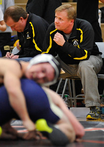 Randy Stukenberg - For the Northwest Herald  Harvard head wrestling coach Tim Haak (right) checks the clock during a match in the Class 1A Wrestling Dual Team Sectional Tuesday, Feb. 19, 2013.