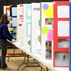 Wredling Middle School sixth grader Elizabeth Quintanar takes notes about a classmate's project during the school's science fair Wednesday afternoon in St. Charles.