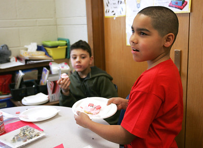 Monica Maschak - mmaschak@shawmedia.com Reginaldo Rivera (right) shows off the pig cookie he made as his third-grade classmate Michael Macias eats his own creation during Farm Day at Locust Elementary School on Friday, February 22, 2013. Students spent the day learning about the shrinking culture of farming with field trips to local farms and fun farm activities.
