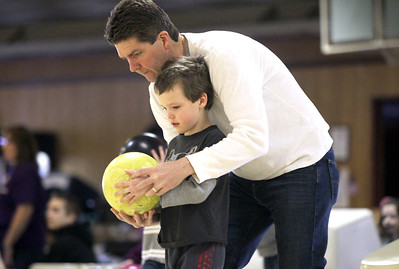Monica Maschak - mmaschak@shawmedia.com Big Brothers Big Sisters Board President Mike Domek guides his son Matthew in bowling for the Bowl for Kids' Sake event at Crystal Bowl on Sunday, February 24, 2013. This is a Big Brothers Big Sisters of McHenry County annual fundraiser to help children who face adversity.