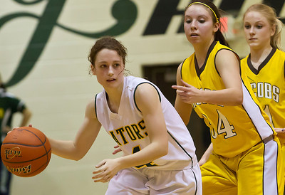 Brett Moist/ For the Northwest Herald        Crystal Lake South's Carina Madoni (4) drives past Jacobs Jennifer Barnec (22) and Lauren Van Blierbergan  during the 4th quarter of gameplay at Crystal Lake South on Friday. Crystal Lake South defeated Jacobs 54-44.