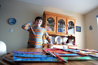 "Monica Maschak - mmaschak@shawmedia.com Matthew Corsaro, 10, stands by his artwork laid out on the dining room table of his family's Lake in the Hills home. Corsaro has autism spectrum disorder and attends Chicago Education Project in Hoffman Estates for schooling and therapy, while his 13-year-old brother, Michael, attends the local public middle school. ""A lot of parents are taking their kids to little league, soccer, basketball and hockey, and we are taking our kid to therapy,"" Corsaro's father, Bruce, said."