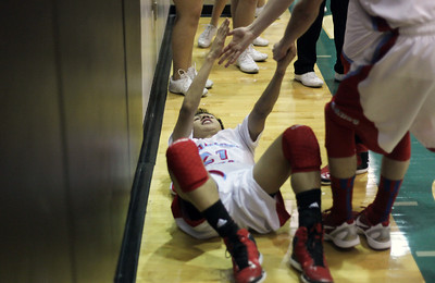 Sarah Nader - snader@shawmedia.com A teammate helps Marian Central's Derreck Caldez up after being knocked down during the fourth quarter of Monday's IHSA 3A Boys Basketball Regional against Harvard in Woodstock on February 25, 2013. Marian Central won, 55-41.