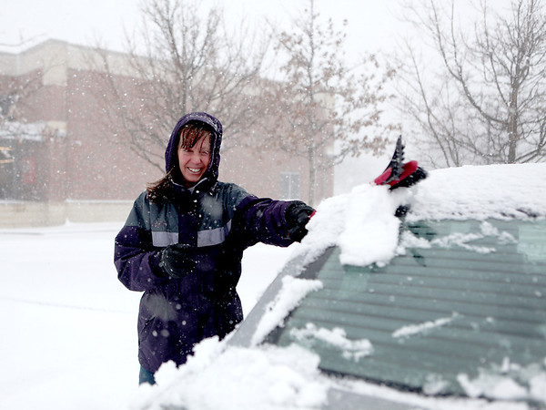 Patty Soutar of St. Charles clears her car of snow in the parking lot of the Aldi food store in Geneva Tuesday afternoon.(Sandy Bressner photo)