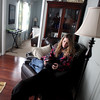 Artist Kerri Branson relaxes with her dog, Raven, in the studio of her North Aurora home.(Sandy Bressner photo)