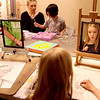 Olivia Henry, 9, works on a self portrait using charcoal as instructor August Vollbrecht helps Ava Moskal, 5, with a painting during a class at the Art Box in Geneva.(Sandy Bressner photo)