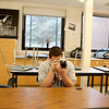 St. Charles East High School sophomore Jesse Israel looks through his camera during a Photography I class at the school. (Sandy Bressner photo)
