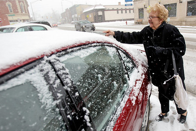 Sarah Nader - snader@shawmedia.com Jean Bowers of Marengo clears her windows from snow after working at a thrift shop in downtown Marengo on Thursday, February 7, 2013. Moderate to heavy snowfall is expected throughout the early evening, according to the weather service.