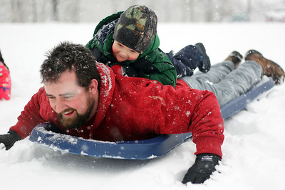Sarah Nader - snader@shawmedia.com George Niespodzianski of Woodstock sleds with his son, George, 2,  at Emricson Park in Woodstock on Thursday, February 7, 2013. Accumulation of 4 to 8 inches was expected to fall on McHenry County.