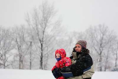 Sarah Nader - snader@shawmedia.com Regina Niespodzianski of Woodstock holds her daughter, Helen, 11, months while sledding with her family at Emricson Park in Woodstock on Thursday, February 7, 2013. Accumulation of 4 to 8 inches fell on McHenry County.