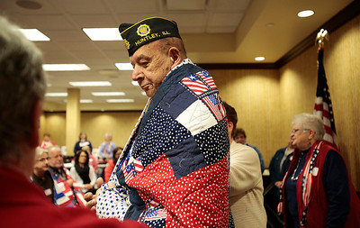 Kyle Grillot - kgrillot@shawmedia.com   Air Force veteran George Hellner of Huntley is presented with the quilt designed for him during the Quilts of Valor presentation Tuesday at American Community Bank in Huntley. The national organization has awarded over 96,000 quilts since 2003. The bank has donated their basement for the group to use on the first Tuesday of every month. Local veterans from many wars were awarded the hand-made quilts Tuesday in Huntley, and there is an application process for other local veterans to receive the award.
